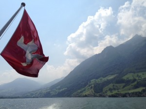 Swiss Flag Waving In Mountain Range