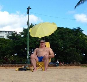 Man under a personal umbrella relaxing