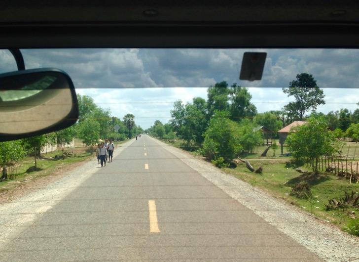 Cambodian school kids walking on the side of the road in 100 degree heat