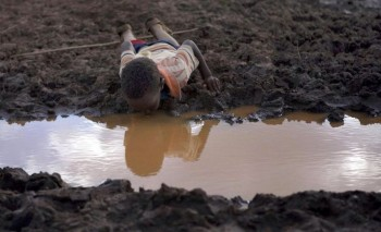 child drinking dirty water